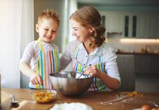 Happy family in kitchen. mother and child preparing dough, bake cookies royalty free stock images