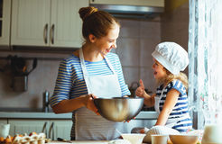 Happy family in kitchen. mother and child preparing dough, bake. Happy family in the kitchen. mother and child daughter preparing the dough, bake cookies royalty free stock photo