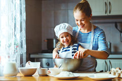 Happy family in kitchen. mother and child preparing dough, bake. Happy family in the kitchen. mother and child daughter preparing the dough, bake cookies royalty free stock images