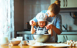 Happy family in kitchen. mother and child preparing dough, bake. Happy family in the kitchen. mother and child daughter preparing the dough, bake cookies royalty free stock image