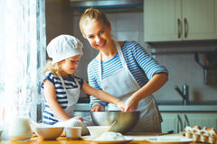 Happy family in kitchen. mother and child preparing dough, bake Stock Images