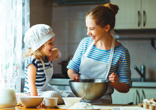 Happy family in kitchen. mother and child preparing dough, bake. Happy family in the kitchen. mother and child daughter preparing the dough, bake cookies royalty free stock photography