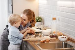 Happy family in kitchen. mother and child baking cookies. Happy family in kitchen. mother and child son baking cookies together Stock Photo