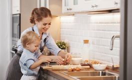 Happy family in kitchen. mother and child baking cookies. Happy family in kitchen. mother and child son baking cookies together Royalty Free Stock Photo