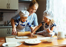 Happy family in kitchen. mother and children preparing dough, ba. Happy family in the kitchen. mother and  children preparing the dough, bake cookies Royalty Free Stock Image