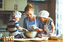 Happy family in kitchen. mother and children preparing dough, ba Royalty Free Stock Images