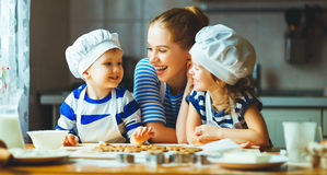 Happy family in kitchen. mother and children preparing dough, ba Stock Images
