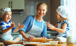 Happy family in kitchen. mother and children preparing dough, ba Stock Photography