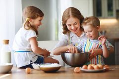 Happy family in kitchen. mother and children preparing dough, bake cookies stock photography