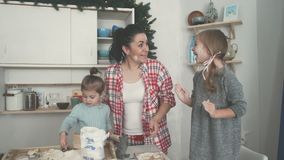 Happy family in the kitchen. Mother and children preparing the dough, bake cookies. Mother and two daughters. Bright kitchen. Preparing food stock video footage