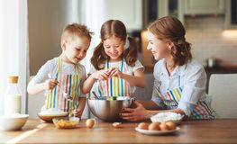 Happy family in kitchen. mother and children preparing dough, bake cookies stock images