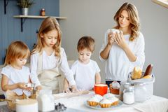Happy family in the kitchen. Mother and her cute kids are cooking cookies stock photo