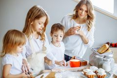 Happy family in the kitchen. Mother and her cute kids are cooking cookies. stock photos