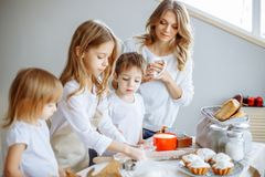 Happy family in the kitchen. Mother and her cute kids are cooking cookies. Happy family in the kitchen. Mother and her cute kids are cooking cookies stock photography