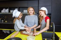 Mother and children cooking in kitchen and having fun royalty free stock photos