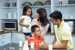 Happy family in the kitchen ready to eat biscuits Stock Photography