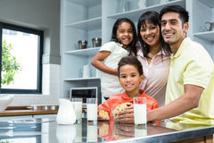 Happy family in the kitchen ready to eat biscuits Stock Photos