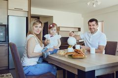 A happy family in the kitchen while sitting at a table. stock images