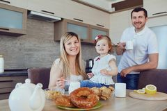 A happy family in the kitchen while sitting at a table. stock photography