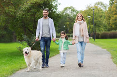 Happy family with labrador retriever dog in park. Family, pet, domestic animal and people concept - happy family with labrador retriever dog walking  in summer Royalty Free Stock Image