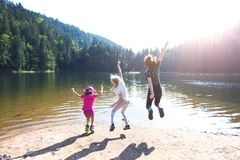 Happy family  at the lake Synevyr. Summer - three sisters on a hike. Fun happy family  jumping on the shore of a mountain lake synevyr royalty free stock photography