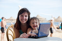 Happy family   with laptop at  beach Royalty Free Stock Photos