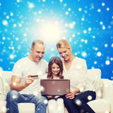 Happy family with laptop computer and credit card Royalty Free Stock Images
