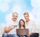 Happy family with laptop computer and credit card Stock Photography