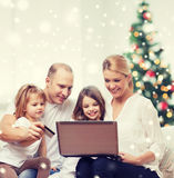 Happy family with laptop and credit card at home. Family, holidays, shopping, technology and people - happy family with laptop computer and credit card over Royalty Free Stock Images