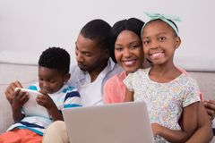 Happy family with laptop and digital tablet sitting on sofa Stock Photo