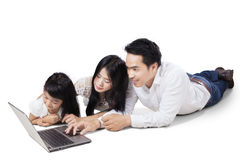 Happy family with laptop on the floor Royalty Free Stock Photos