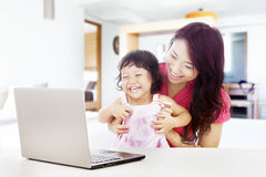 Happy family with laptop at home. Shot of happy young mother and daughter with ultrabook laptop computer. shot at home Royalty Free Stock Photos