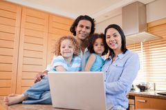 Happy family with laptop standing in the kitchen together Royalty Free Stock Images