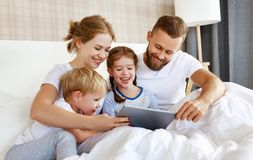 Happy family laughing with tablet computer in bed at home. watching movies and   Internet