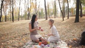 Happy mom and daughter have fun in the city park. Family laughs and juggles apples to each other. stock footage