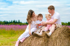Happy family launching toy sitting on haystack Stock Image