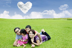 Happy family laying on the grass Stock Images