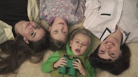 Happy family laying on the floor on fluffy carpet, smiling. Mother and kids are happy. Funny little boy in pajamas looks stock video