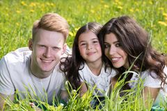 Happy family laying on grass stock image