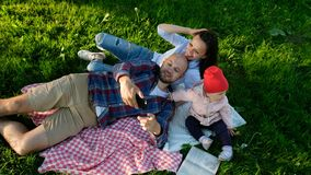 Happy family is laying on the pled and doing selfie with a baby at sunset in the park. Father and mother take pictures stock image