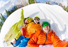 Happy family laying in snow and making selfie Stock Photography