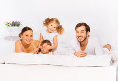 Happy family laying on white bed in pajamas Stock Photo