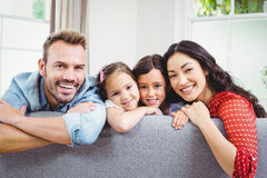 Happy family leaning on sofa at home. Portrait of happy family leaning on sofa at home Stock Photos