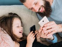 Happy family leisure dad kid laugh together phone. Happy family leisure and gratifying rewarding fatherhood. dad and daughter sharing a laugh together after royalty free stock image