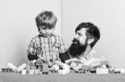 Happy family. family leisure time. child development. building home with colorful constructor. father and son play game. Happy little boy with bearded man dad royalty free stock image