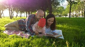 Happy family lies on the grass and read a book at a picnic and play with the child at sunset in the park.  Royalty Free Stock Photo