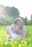 Happy Family Life Concepts and Ideas. Caucasian Brunette Mother with Her Toddler Son Spending Time Together. Outdoors Embraced in Park. Vertical Image Stock Photography