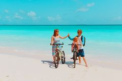 Happy family with little baby girl riding bikes on beach royalty free stock photos