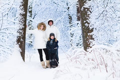 Happy family with little boy walking in snowy park. Happy young family with a cute little boy walking in a snowy park Royalty Free Stock Images