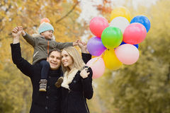 Happy family. With little child and air-balloons, outing in autumn park royalty free stock photography